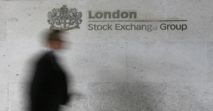 FILE PHOTO: A man walks past the London Stock Exchange in the City of London