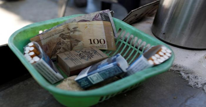Venezuelan bolivar notes and cigarettes on sale are seen in a basket in downtown Caracas