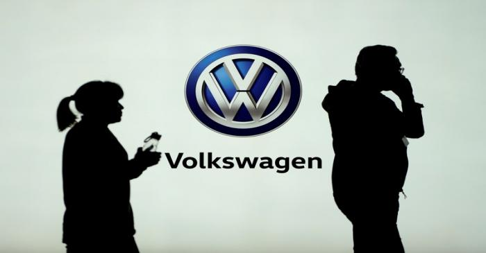 FILE PHOTO: People pass in front of a Volkswagen logo ahead of the Shanghai Auto Show