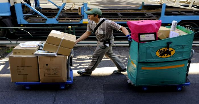 FILE PHOTO: A delivery man moves carts with parcels in Tokyo