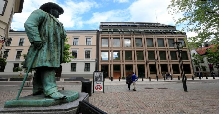 People go about their day near Norway's central bank building in Oslo