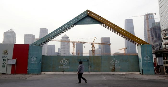 FILE PHOTO: A man walks outside the construction sites in Beijing's central business area