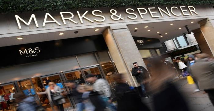 Shoppers walk past a branch of Marks and Spencer in central London, Britain