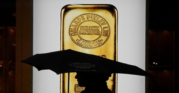 A pedestrian walks past a window displaying a representation of a gold bar at a bullion broker