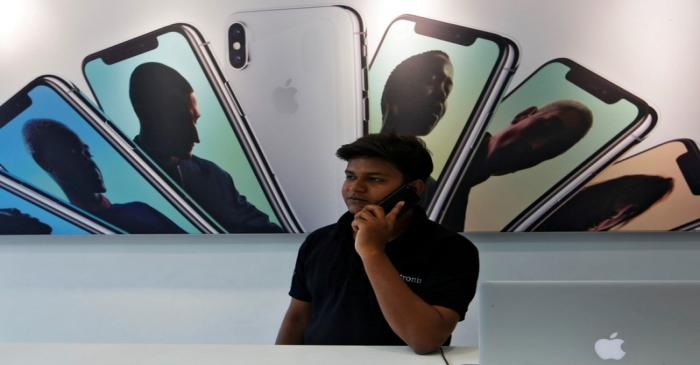 FILE PHOTO: Salesperson speaks on the phone at an Apple reseller store in Mumbai