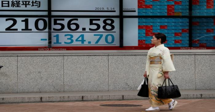 A woman wearing a kimono walks past an electronic board showing the Nikkei stock index outside