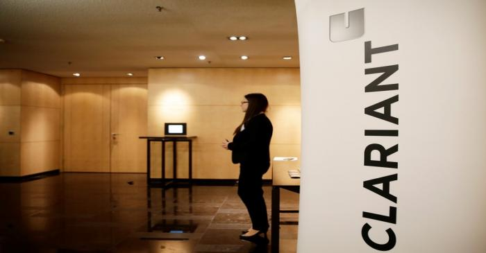 Woman stands next to logo of Swiss specialty chemicals company Clariant ahead of a news