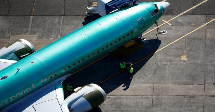 Workers gather next to an unpainted Boeing 737 MAX aircraft seen parked at Renton Municipal