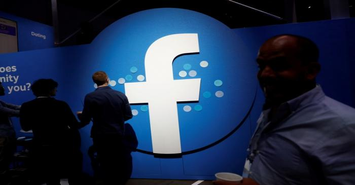 FILE PHOTO: Attendees walk past a Facebook logo during Facebook Inc's F8 developers conference