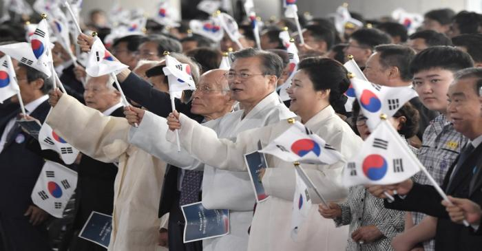 South Korean President Moon Jae-in and his wife Kim Jung-sook wave the national flags during a