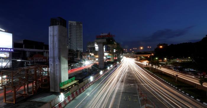 Cars pass Skytrain construction site in Bangkok