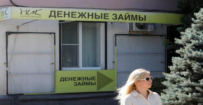 A woman walks past an office of a local lending agency in Stavropol