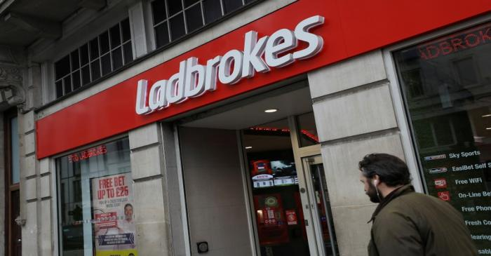 FILE PHOTO: A pedestrian walks past a branch of Ladbrokes in London