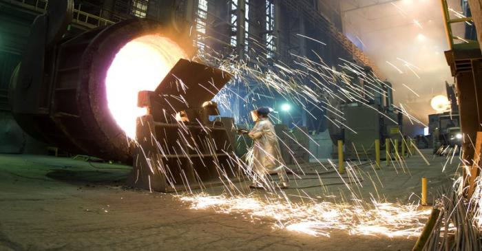FILE PHOTO - A worker cleans an industrial container for molten steel at the ArcelorMittal