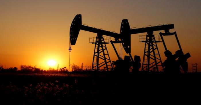 FILE PHOTO:  Pumpjacks are seen against the setting sun at the Daqing oil field in Heilongjiang