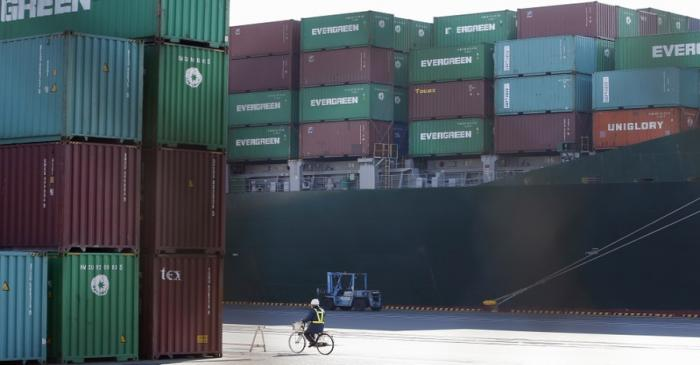 A man rides a bicycle past containers and a cargo ship at a port in Tokyo