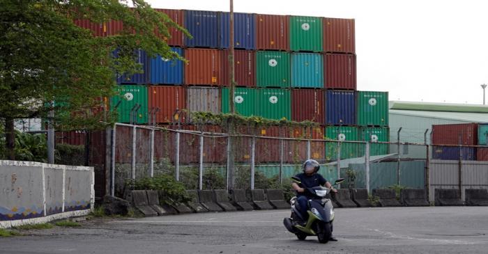 A man rides a motorbike near Kaohsiung Port