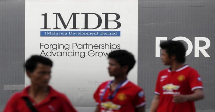 FILE PHOTO: Men walk past a 1Malaysia Development Berhad (1MDB) billboard at the fund's