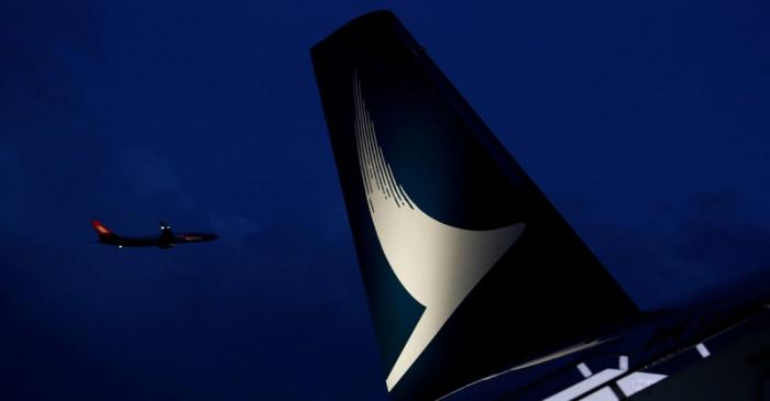 FILE PHOTO: Plane flies behind a new Cathay Pacific Airways Airbus A350 after being received by