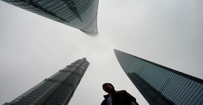 Man walks by skyscrapers at Lujiazui financial district in Shanghai