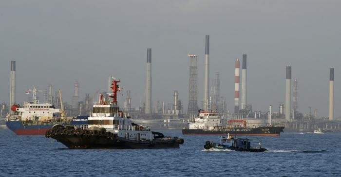Vessels pass an oil refinery in the waters off the southern coast of Singapore