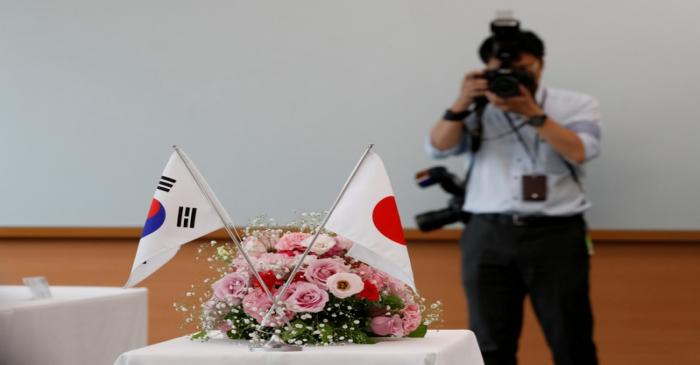 FILE PHOTO: National flags of South Korea and Japan are displayed during a meeting between