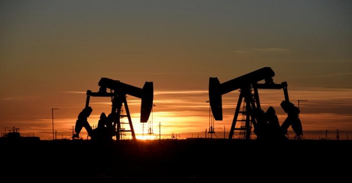 FILE PHOTO: Pump jacks operate at sunset in an oil field in Midland, Texas