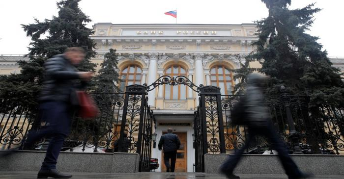 People walk past the headquarters of Russia's Central Bank in Moscow