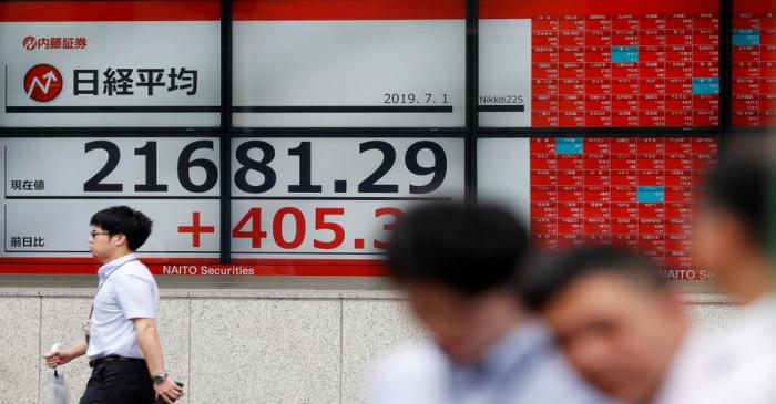 Passerbys walk past an electric screen showing Japan's Nikkei share average outside a brokerage