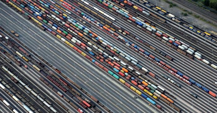 Containers and cars are loaded on freight trains at the railroad shunting yard in Maschen near