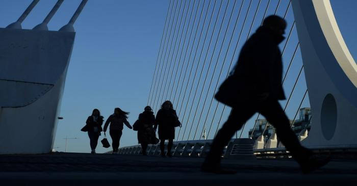 Commuters make their way into work in the morning in the financial district of Dublin