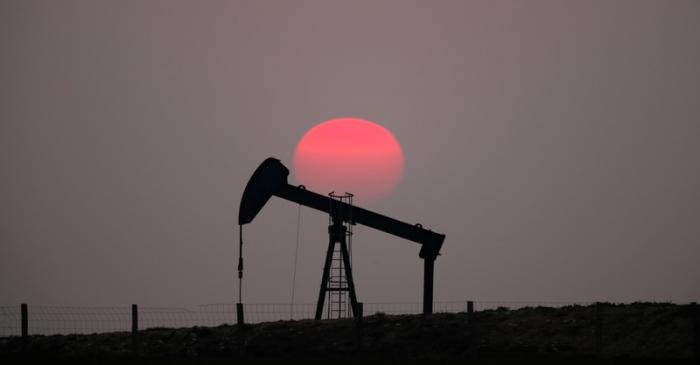 The sun sets behind a pump-jack outside Saint-Fiacre