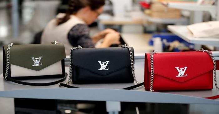 FILE PHOTO: Louis Vuitton handbags are displayed as an employee works in a Vuitton new high-end
