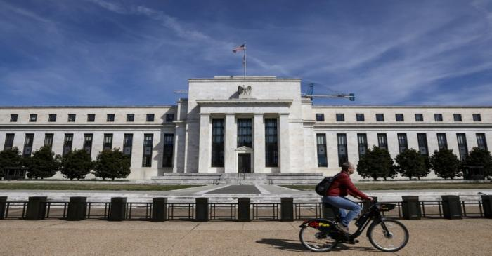 FILE PHOTO: A man rides a bike in front of the Federal Reserve Board building on Constitution