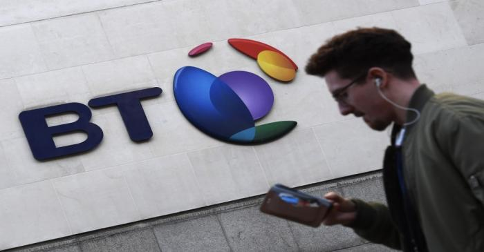 A man walks past a BT logo outside of offices in the City of London