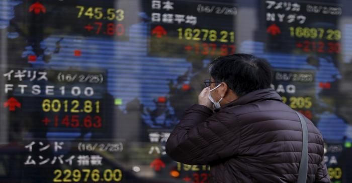 A pedestrian looks at an electronic board showing the stock market indices of various countries