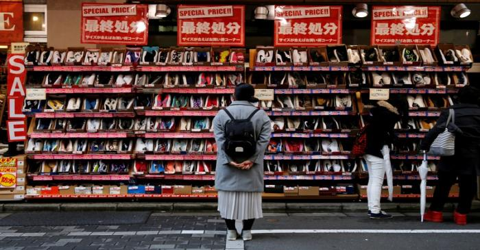 A woman looks at shoes on sale at an outlet store in Tokyo's shopping district