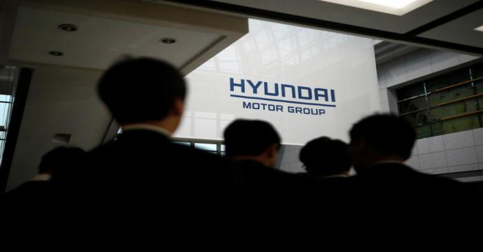 Employees of Hyundai Motor walk past the company's logo after the company's New Year ceremony