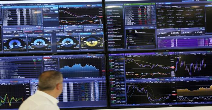 FILE PHOTO: A trader works as a screen shows market data behind him in London