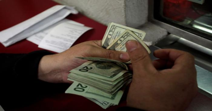 Employee counts U.S. dollar banknotes at a foreign exchange house in Monterrey