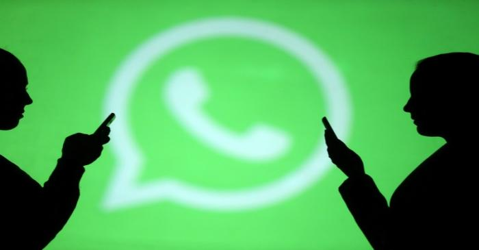 Silhouettes of mobile users are seen next to a screen projection of Whatsapp logo in this