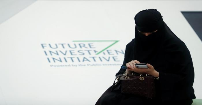 A Saudi woman uses her phone during the Future Investment Initiative conference in Riyadh