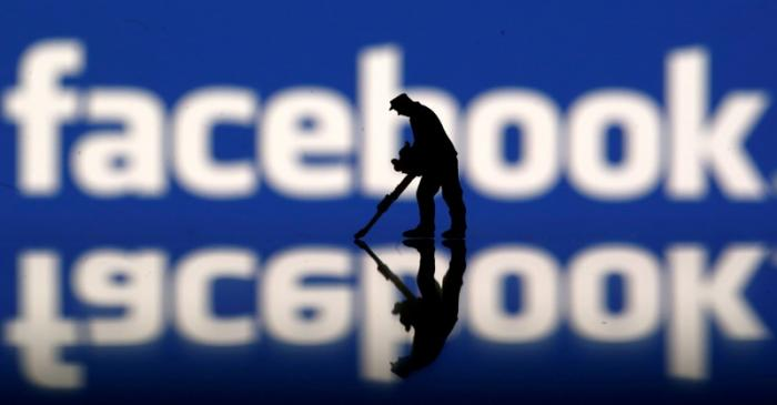 FILE PHOTO: A figurine is seen in front of the Facebook logo in this illustration