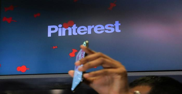 A guest hold up a phone during the Pinterest Inc. IPO on the floor of the NYSE in New York