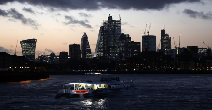A river boat cruises down the River Thames as the sun sets behind the Canary Wharf financial