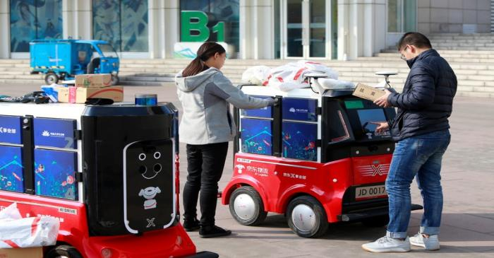 FILE PHOTO: People retrieve their parcels from a JD.com driverless delivery robot a day after