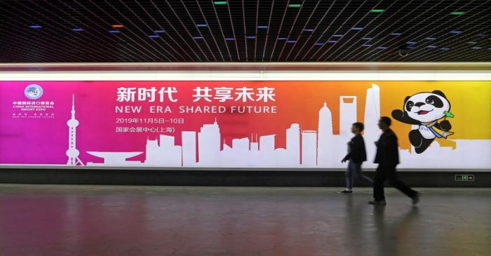 People walk past an advertisement for the upcoming China International Import Expo at a train