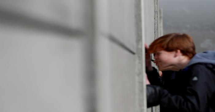 FILE PHOTO: Visitors peers through segments of Wall at the Berlin Wall memorial on Bernauer