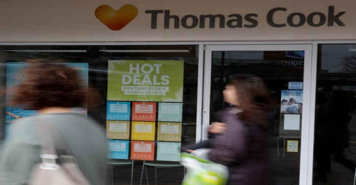 People walk past a closed Thomas Cook travel agents store near Manchester, Britain