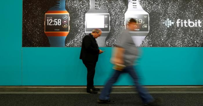 FILE PHOTO: Visitors walk past an advertising billboard for Fitbit Ionic watches at the IFA